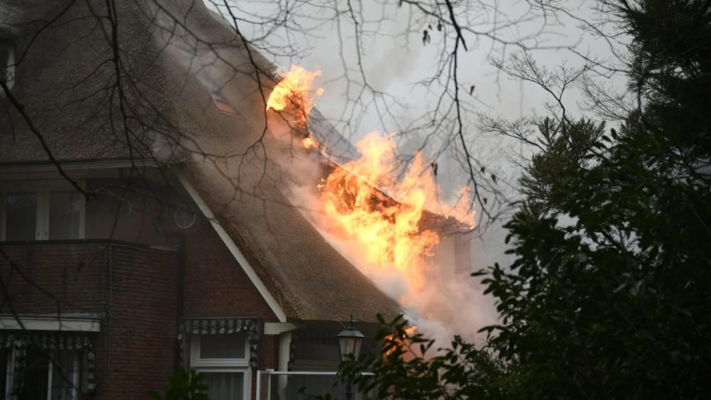 Grote uitslaande brand in Bussumse villa: vlammen slaan hoog uit het dak