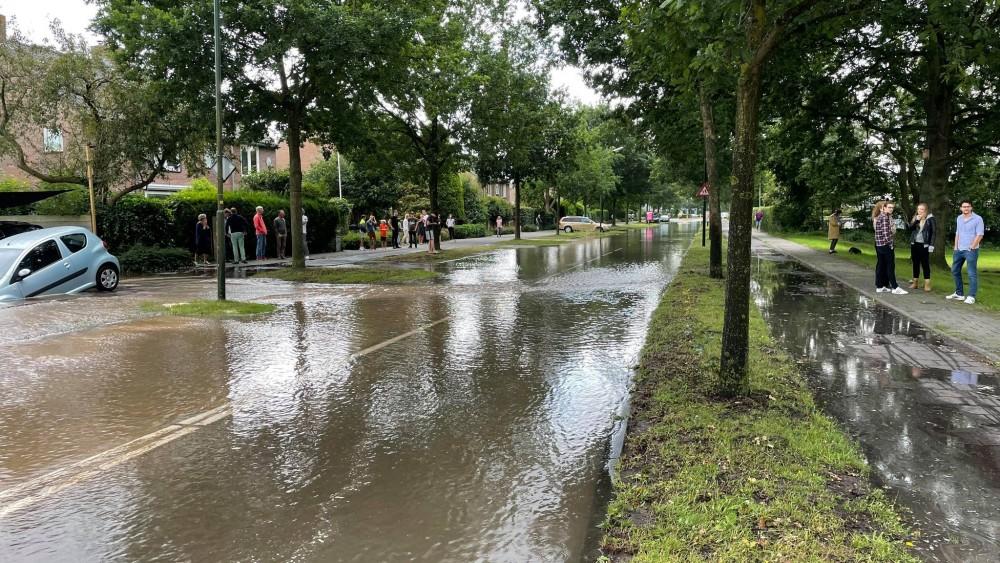 Gesprongen waterleiding zet straat blank in Naarden, auto kukelt in sinkhole